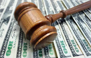 A judge;s gavel sitting on $100 bills