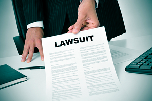 "A man with a suit hold a piece of paper that says ""lawsuit"""