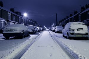 A snowy street with cars parked on either side.