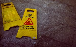 "A knocked-over ""caution - cleaning in progress"" sign"