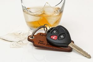 A broken glass of liquor and car keys