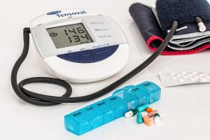 A blood pressure monitor, pill case, and medications on a table