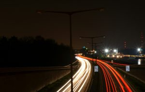 Time-lapse photo of street at night showing streaks of headlights and taillights
