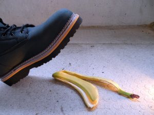 A booted foot about to step onto a banana peel
