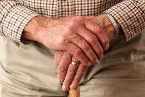an elder's hands holding a cane