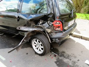 A black minivan with damage to the rear