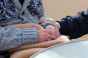 A young person holding an older person's hand
