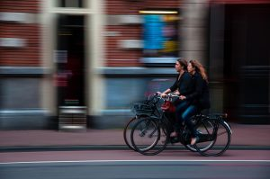 Two cyclists biking on a street