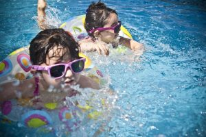 Two young girls swimming in a pool
